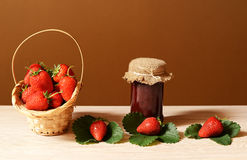 Fresh strawberries in a wicker basket and jam in a jar Stock Photos