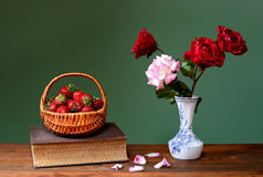 Fresh strawberries in wicker baskets and roses Royalty Free Stock Image