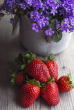 Fresh strawberries are on the wood with campanula. In grey pot as background Stock Photo