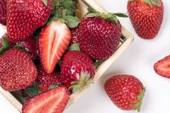 Fresh strawberries in wooden basket on white background stock photography
