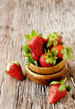 Fresh strawberries in a wooden bowl, selective focus Stock Photo