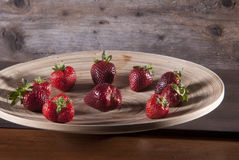 Fresh strawberries on a wooden plate Stock Photo