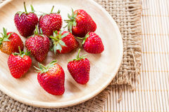 Fresh strawberries in wooden plate on wooden table Stock Images