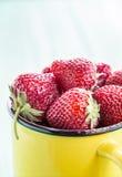 Fresh strawberries in a yellow mug Stock Photo