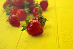 Fresh strawberries on the yellow wooden table. Fresh strawberries on the bright yellow wooden table Stock Photos