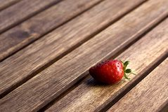 Fresh Strawberry. A single red strawberry on teak table stock image