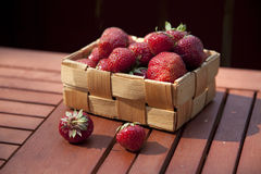 Fresh strawberry in basket on wooden table Stock Images