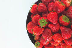 Fresh strawberry In a black cup and white background. Stock Images