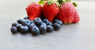 Fresh strawberry and blueberry mix on a metal dish over a rough rustic wood background Stock Photos