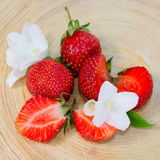 Fresh strawberry on the board. Fresh whole and sliced ​​strawberries with flowers on the board royalty free stock photos