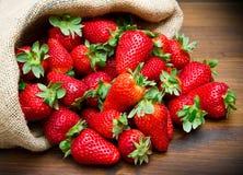Fresh strawberry in burlap sack on wood Royalty Free Stock Photo