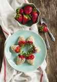 Fresh strawberry coated in yogurt and cookies crumble. On wooden table Stock Photo