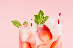 Fresh strawberry cocktailы with spiced berries, ice cubes, mint and striped straw on soft pink color, closeup, top section, edge. Fresh strawberry cocktail stock image