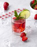 Fresh strawberry cocktail with mint and lime. Summer drink with ice cubes and straw on marble background royalty free stock photography