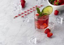 Fresh strawberry cocktail with mint and lime. Summer drink with ice cubes and straw on marble background stock image