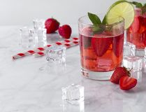 Fresh strawberry cocktails with mint and lime. Summer drinks with ice cubes and straw on marble background stock photos