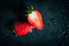 Fresh strawberry cut in half on dark ceramic tile (top view) Stock Photo