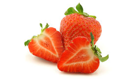 Fresh strawberry and a cut one stock photography