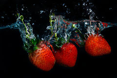 Fresh strawberry dropped into water with splash on black backgro Royalty Free Stock Photography