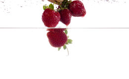Fresh strawberry dropped into water with splash Stock Photo