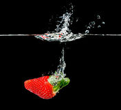 Fresh strawberry dropping into water Royalty Free Stock Photo