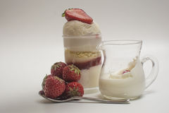 Fresh strawberry falling down into splashing milk near dessert Royalty Free Stock Photography