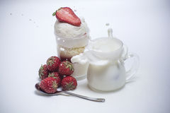Fresh strawberry falling down into splashing milk near dessert Stock Image