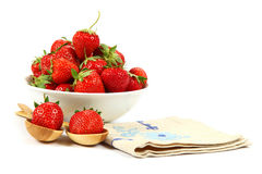 Fresh strawberry fruit in a white dish with a wooden spoon. Royalty Free Stock Photography