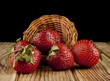 Fresh strawberry fruit on a wooden table isolated on a black. Background Stock Photos