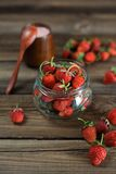 Fresh strawberry in a glass jar. On a wood background Stock Images