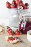 Fresh Strawberry Jam. A farmhouse kitchen table scene of freshly made strawberry jam in storage jar with a tin pail of strawberries in the background and bread stock photography