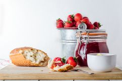 Fresh Strawberry Jam Snack Scene with Bucket of Strawberries. A kitchen table scene of freshly made strawberry jam in storage jar with a tin pail of strawberries royalty free stock photos