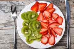 Fresh strawberry and kiwi slices on cutting plate Royalty Free Stock Image