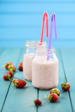 Fresh strawberry milk cocktail in mason jars with straws on blue Royalty Free Stock Photography