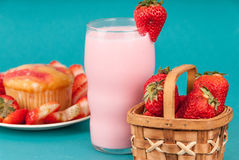 Fresh Strawberry Muffin with Strawberry milk. Fresh strawberries cut sliced around a strawberry muffin wth a basket of strawberries on a white plate on a blue Stock Image