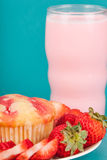 Fresh Strawberry Muffin with Strawberry milk. Fresh strawberries cut sliced around a strawberry muffin wth a few whole strawberries on a white plate on a blue Royalty Free Stock Photography