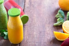 Fresh strawberry, orange and broccoli smoothie in bottles with green caps with fruits and vegetables on a brown wooden rustic back. Fresh strawberry, orange and Royalty Free Stock Photos