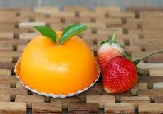 Fresh Strawberry and Orange cake on wood mat. Royalty Free Stock Photos