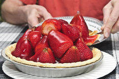 Fresh Strawberry Pie. A man's hands are seen cutting a slice of strawberry pie and lifting out the slice from the pie, with whole very large fresh strawberries Royalty Free Stock Photography