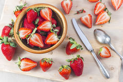 Fresh strawberry pieces cut by vintage knife country style. Strawberry pieces in brown bowl and cut on board country style Royalty Free Stock Photos