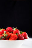 Fresh strawberry in plate on black background Royalty Free Stock Photography
