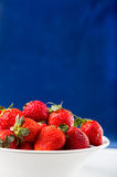 Fresh strawberry in plate on blue background Stock Image