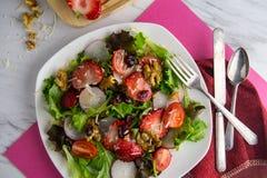 Fresh Strawberry Salad. Fresh organic romaine lettuce salad with walnuts radishes and strawberries Stock Photo