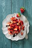 Fresh strawberry salad with red balsamic vinaigrette dressing. On white dessert plate there is fresh strawberry salad with red balsamic vinaigrette dressing stock photos