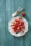 Fresh strawberry salad with red balsamic vinaigrette dressing. On white dessert plate there is some fresh strawberry salad with red balsamic vinaigrette Royalty Free Stock Photo