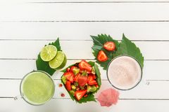 Fresh strawberry smoothies and vegetable green smoothies with lime and mint near a fruit salad of strawberries, kiwi. And pomegranate on wooden boards. Top view royalty free stock photos