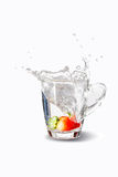 A fresh strawberry splashing water. A fresh strawberry splashing in a glass with water Royalty Free Stock Images