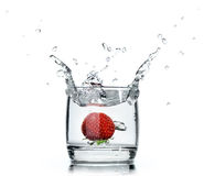 A fresh strawberry splashing water in a glass on white Stock Photos