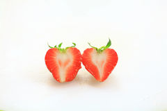 Fresh strawberry, sweet fruits, on the white plastic chopping board, heart and love concept. Stock Images