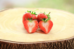 Fresh strawberry, sweet fruits, whole and cut in half, on the wooden chopping board. Royalty Free Stock Photos